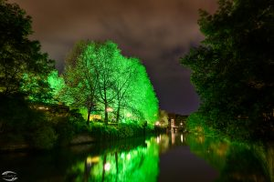 View over river Pegnitz with green illuminated trees at the city beach.