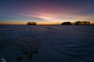 Twilight over a frozen lake with some islands in the background