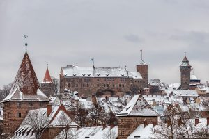 Picture of the snow covered Imperial Castle of Nuremberg with parts of the snow covered old town in the foreground