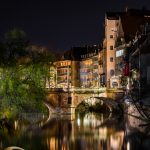 View along a river to a bridge at night