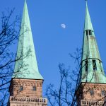 The moon between two towers during daytime
