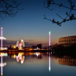 View over a lake to a fun fair at night